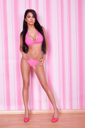 Beautiful sexy shapely woman with a sultry look modeling a pink bikini in front of a striped pink studio background photo