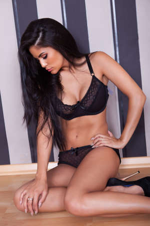 tantalizing: Beautiful seductive woman in black lingerie and stilettos sitting on a wooden floor against a black striped studio background Stock Photo