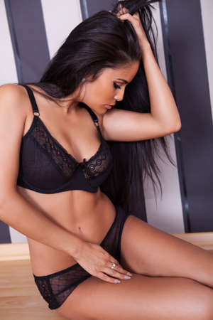 black bra: Beautiful seductive woman in black lingerie and stilettos sitting on a wooden floor against a black striped studio background Stock Photo