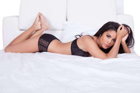 pies sexis: Hermosa mujer sexy en lencería negro tumbado boca abajo en su cama, con los pies en el aire Foto de archivo
