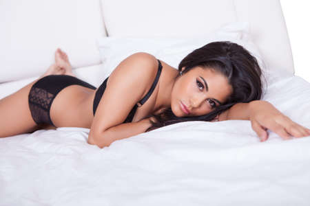 bare women: Beautiful sexy woman in black lingerie lying on her stomach on her bed with her feet in the air Stock Photo