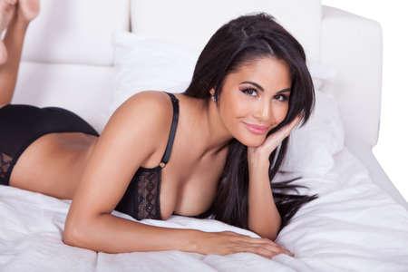 pies sexis: Hermosa mujer sexy en lencer�a negro tumbado boca abajo en su cama, con los pies en el aire Foto de archivo