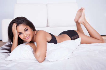 bedclothes: Beautiful brunette woman with a lovely smile relaxing on her stomach on her bed with her chin resting in her hands