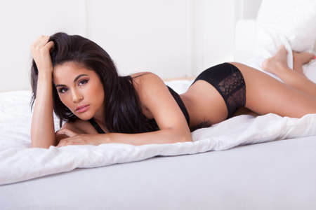 lying on the stomach: Beautiful sexy woman in black lingerie lying on her stomach on her bed with her feet in the air Stock Photo