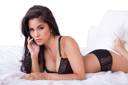 sexy underwear: Beautiful sexy woman in black lingerie lying on her stomach on her bed with her feet in the air Stock Photo