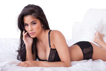 donna sexy: Bella donna sexy in lingerie nera sdraiato a pancia in gi� sul letto con i piedi in aria