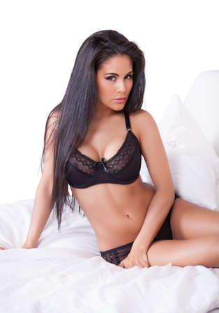 lenceria: Hermosa mujer sexy en lencería negro tumbado boca abajo en su cama, con los pies en el aire Foto de archivo