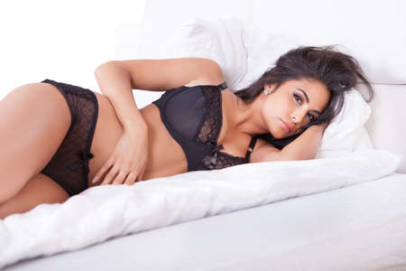lying on stomach: Beautiful sexy woman in black lingerie lying on her stomach on her bed with her feet in the air Stock Photo