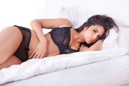 panties: Hermosa mujer sexy en lencer�a negro tumbado boca abajo en su cama, con los pies en el aire Foto de archivo