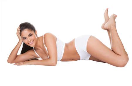 vrouw ondergoed: Mooie dame met een lieve glimlach lag in haar ondergoed. Geà ¯ soleerd op wit