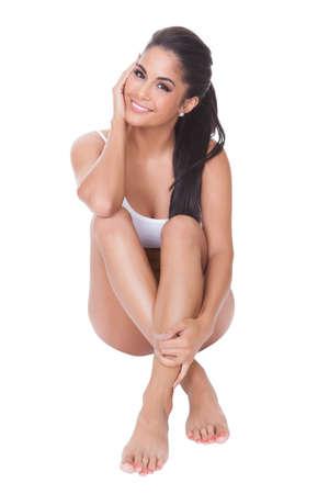 vrouw ondergoed: Mooie blote voeten vrouw zittend op de vloer met haar lange welgevormde benen gekruist voor haar het dragen van haar lingerie Stockfoto