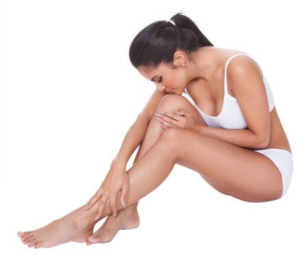 benen: Mooie blote voeten vrouw zittend op de vloer met haar lange welgevormde benen gekruist voor haar het dragen van haar lingerie Stockfoto