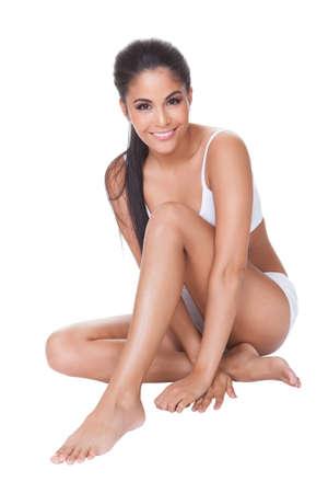 Mooie blote voeten vrouw zittend op de vloer met haar lange welgevormde benen gekruist voor haar het dragen van haar lingerie Stockfoto