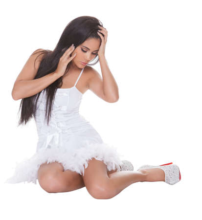white trim: Sexy beautiful woman in a party outfit or cocktail dress trimmed with feathers wearing stilettos posing on a white studio background