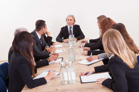 board meeting: Portrait Of A Serious Business Men And Women Attending A Seminar Stock Photo