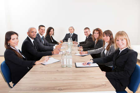 board room: Portrait Of A Serious Business Men And Women Attending A Seminar Stock Photo