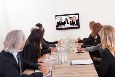 corporation: Businesspeople Sitting At Conference Table Looking At Flat Screen Display Stock Photo