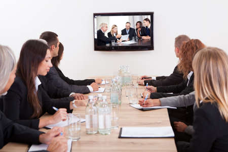 conference room meeting: Businesspeople Sitting At Conference Table Looking At Flat Screen Display Stock Photo
