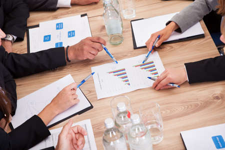 business consulting: Close-up of Businesspeople Sitting At Conference Table Communicating Stock Photo