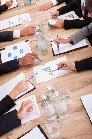 project manager: Close-up of Businesspeople Sitting At Conference Table Communicating Stock Photo