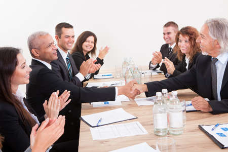 Business Team Sitting At Table And Applauding During Presentation photo