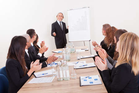 associates: Business Team Sitting At Table And Applauding During Presentation