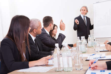 Businessman Raising His Hand Up At A Conference photo