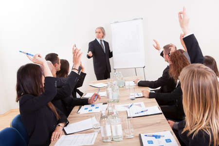 employee training: Businessman Raising His Hand Up At A Conference