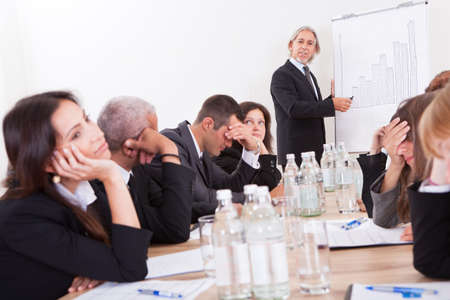 bored man: Photo Of Sad Business Team Attending The Seminar Stock Photo