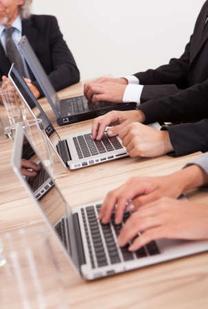 Close-up Shot Of Businesspeople Using Laptop At Conference Table photo