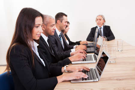 Businesspeople Sitting At Conference Table Using Laptop photo