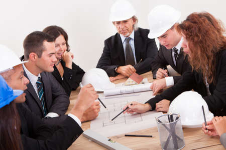 Engineers Discussing About A New Project Around A Table Pointing At A Section On The Blueprint Stock Photo - 15404273