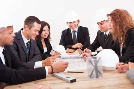 Engineers Discussing About A New Project Around A Table Pointing At A Section On The Blueprint Stock Photo - 15404153
