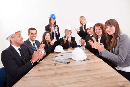 people clapping: Business Team Sitting At Table And Applauding During Presentation