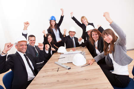 female architect: Portrait Of Engineers Sitting At Table Cheering Stock Photo