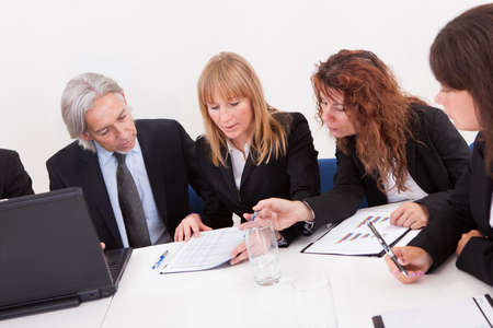 round table: Businesspeople Sitting At Conference Table At The Meeting