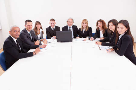 round table conference: Businesspeople Sitting At Conference Table At The Meeting