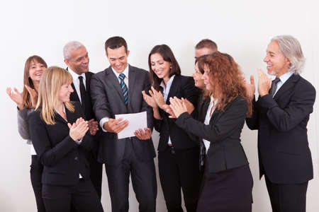 employee satisfaction: Business Team Applauding For The Success Of Colleague