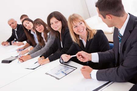 Gesch�ftsmann Aush�ndigung einer Visitenkarte an ein Businesswoman In Meeting Lizenzfreie Bilder