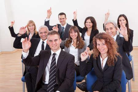 preguntando: Gente de negocios levantando la mano en un seminario