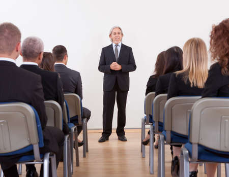 training seminar: Portrait Of A Senior Manager Giving Presentation To His Colleagues Stock Photo