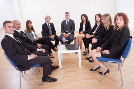 large group of business people: Successful Happy Business People Sitting On Chairs In Meeting Stock Photo