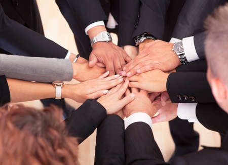 company merger: Group Of Business People With Their Hands Together