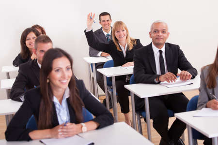 Businesswoman Raising Her Hand In Meeting To Ask Question photo