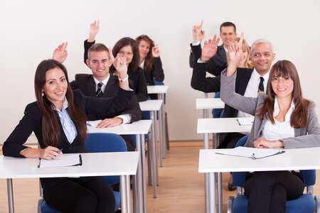 Csoport üzletemberek kézfeltartással A Meeting Stock fotó