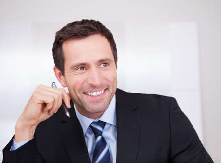 Portrait Of Happy Businessman At Workplace In the Office photo