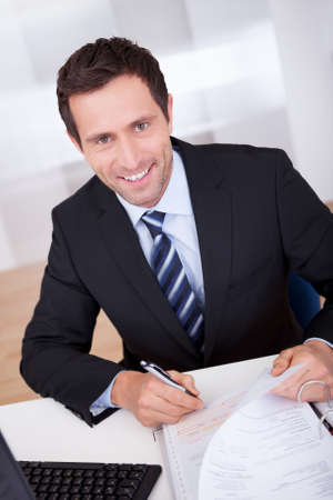 invoice: Portrait Of Happy Accountant At Workplace In The Office Stock Photo