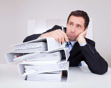overloaded: Bored Businessman Overwhelmed By Paperwork In The Office