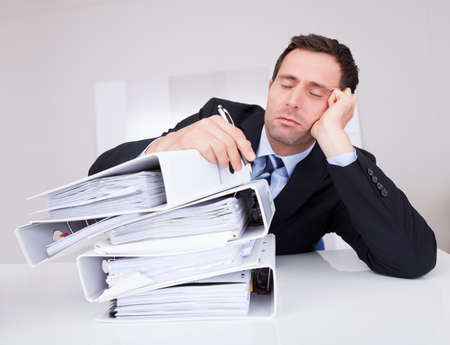 tired businessman: Bored Businessman Overwhelmed By Paperwork In The Office