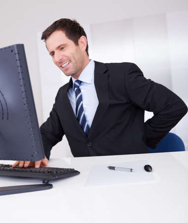 Portrait Of Happy Businessman Using Computer At Workplace Stock Photo - 15403662